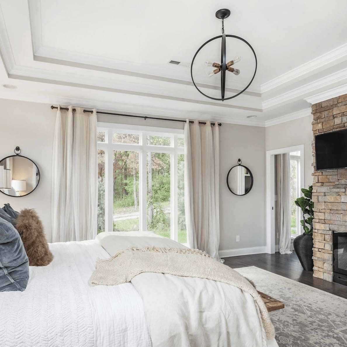 A bedroom with a brick fireplace, a large window, and a bed with decorative pillows and blankets on top