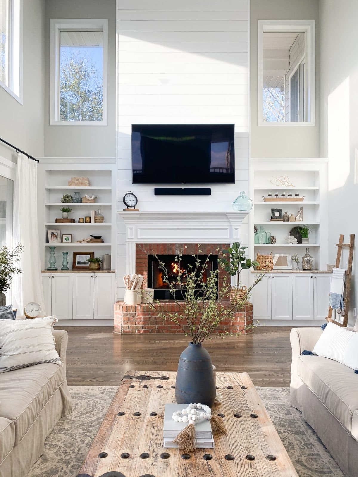 two story living room with fireplace and built ins and the walls painted Repose Gray