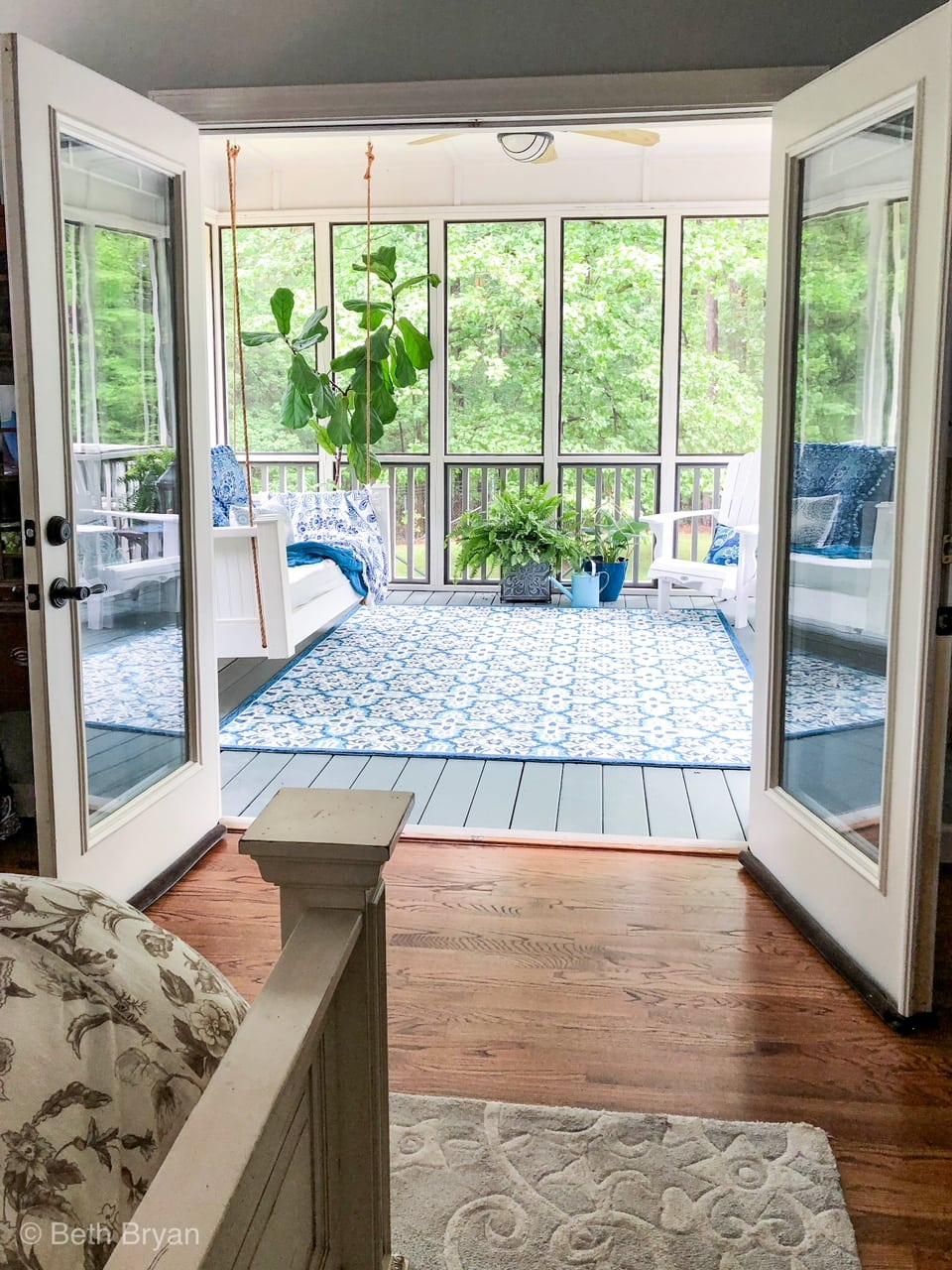 Blue and white porch decor with hanging swing and adirondack chairs