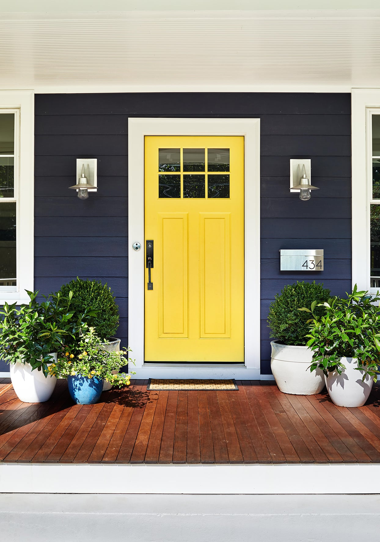 A house with navy side and a bright yellow door