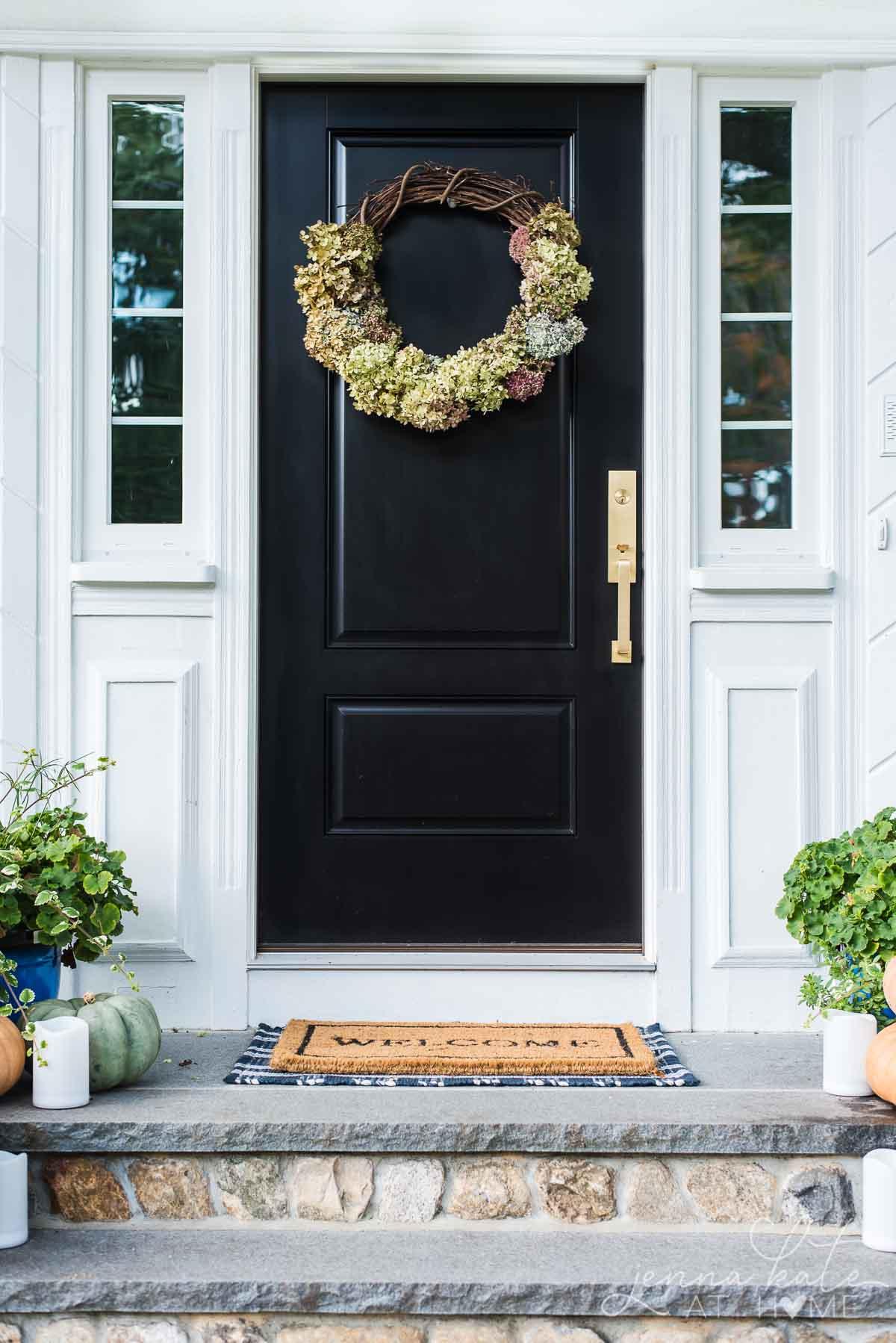diy hydrangea wreath hanging on a black front door