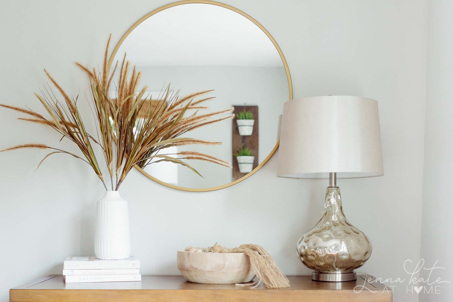 simple fall vignette with dried grass in a vase, a bowl with wooden beads and a mercury glass lamp