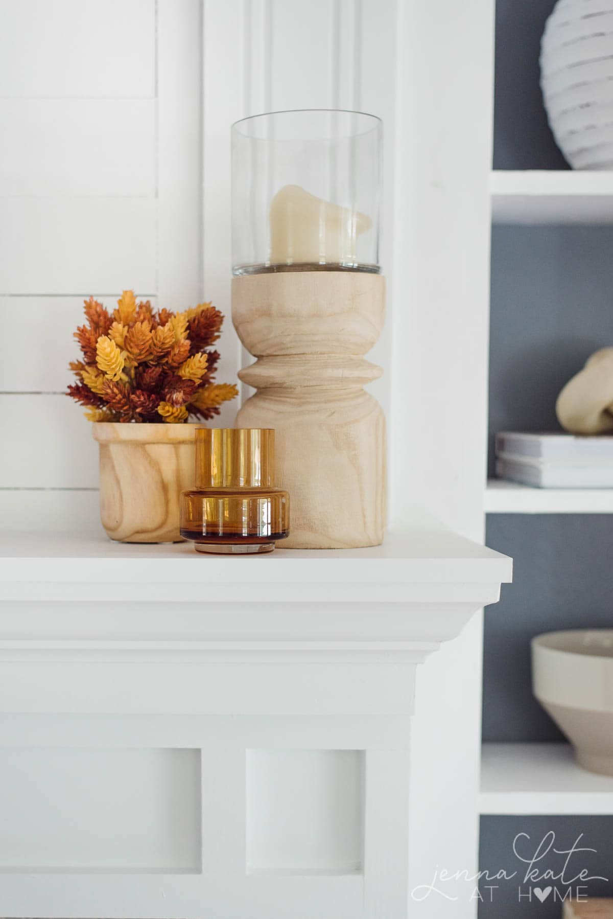 wooden candle holder, faux fall flowers and amber glass on a mantel
