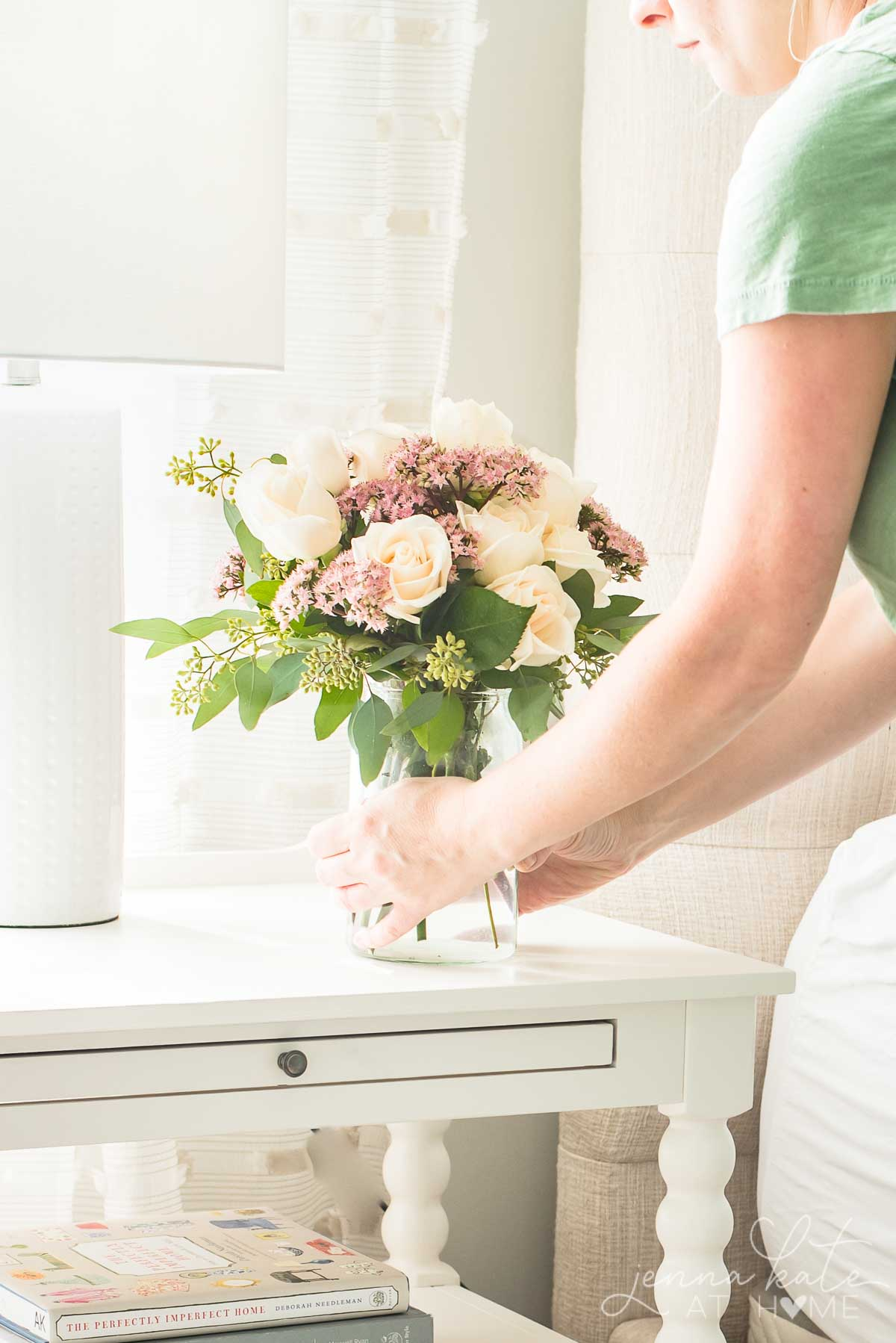Fall flower arrangement of roses and eucalyptus on a bedroom nightstand