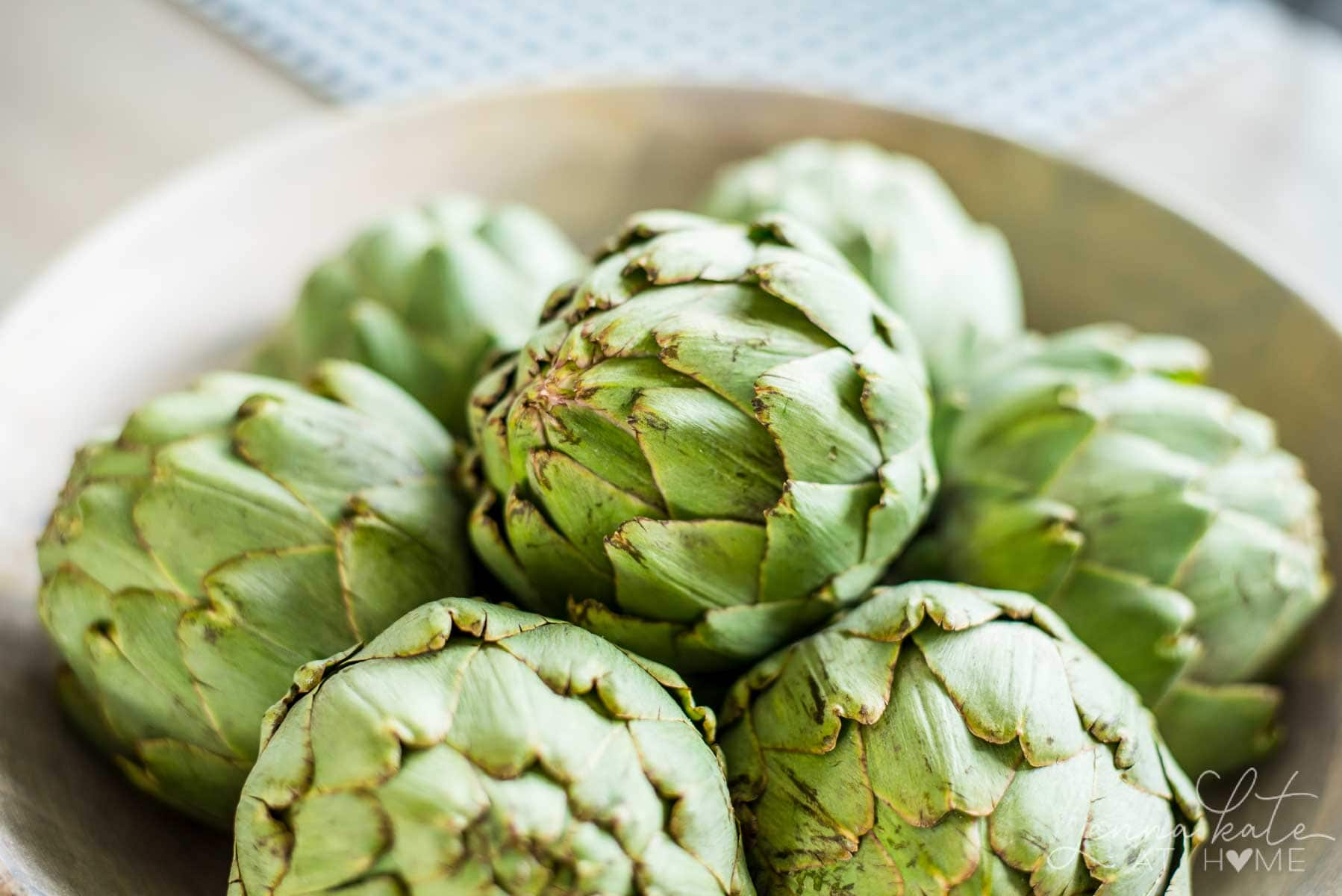 A wooden bowl filled with artichokes