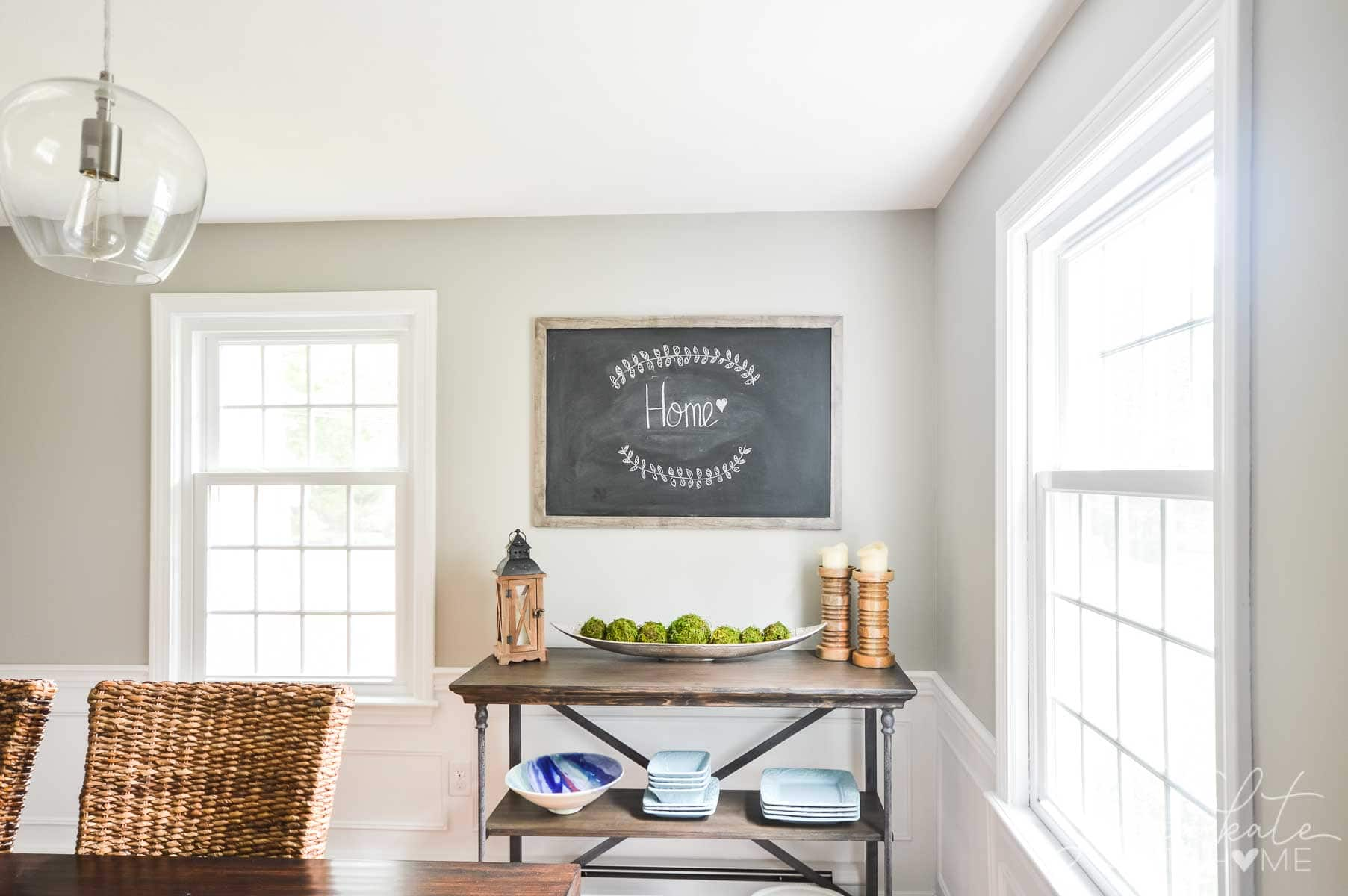 A corner of the dining room with a blackboard displaying chalk art and a side table with various decor items and extra plates/bowls
