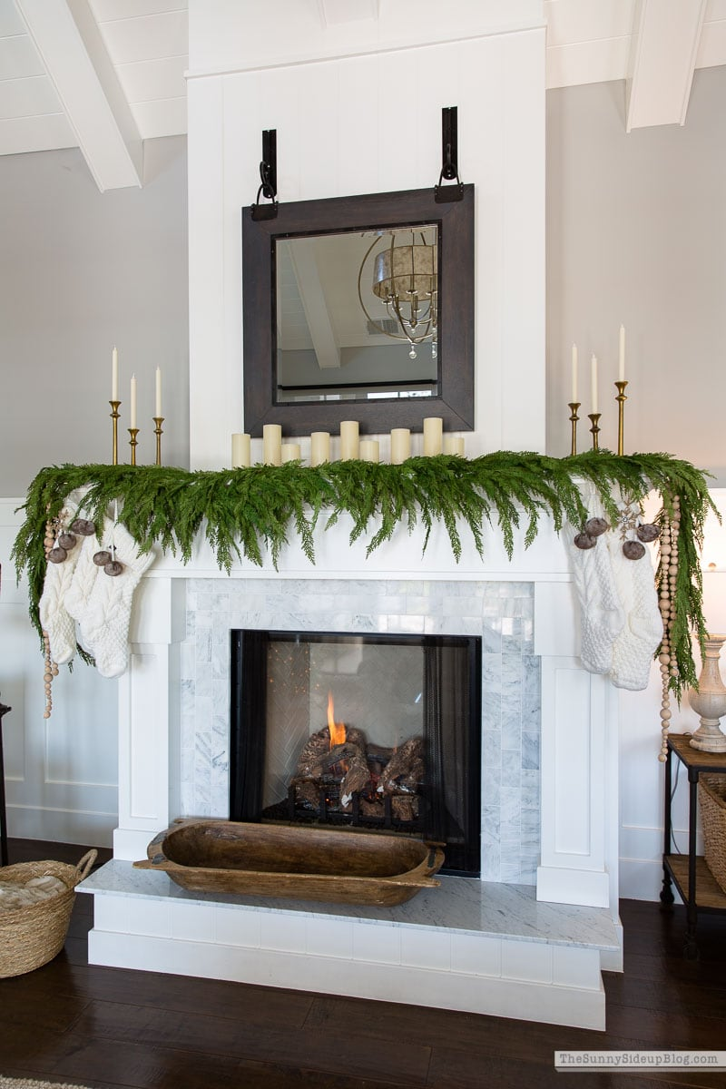 Faux garland draping down the sides and front of a mantel decorated for Christmas