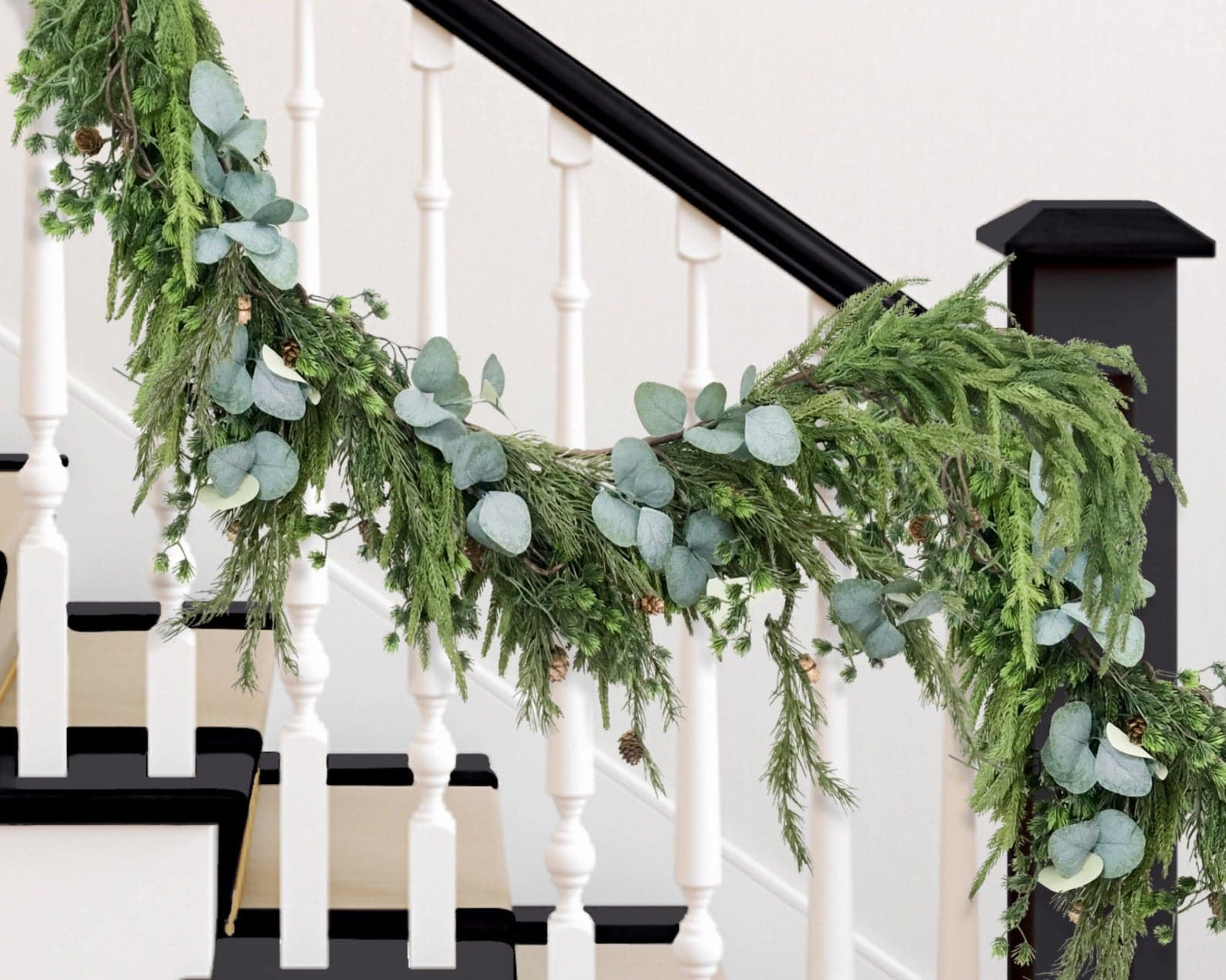 Pine and eucalyptus garland hanging from stair bannister
