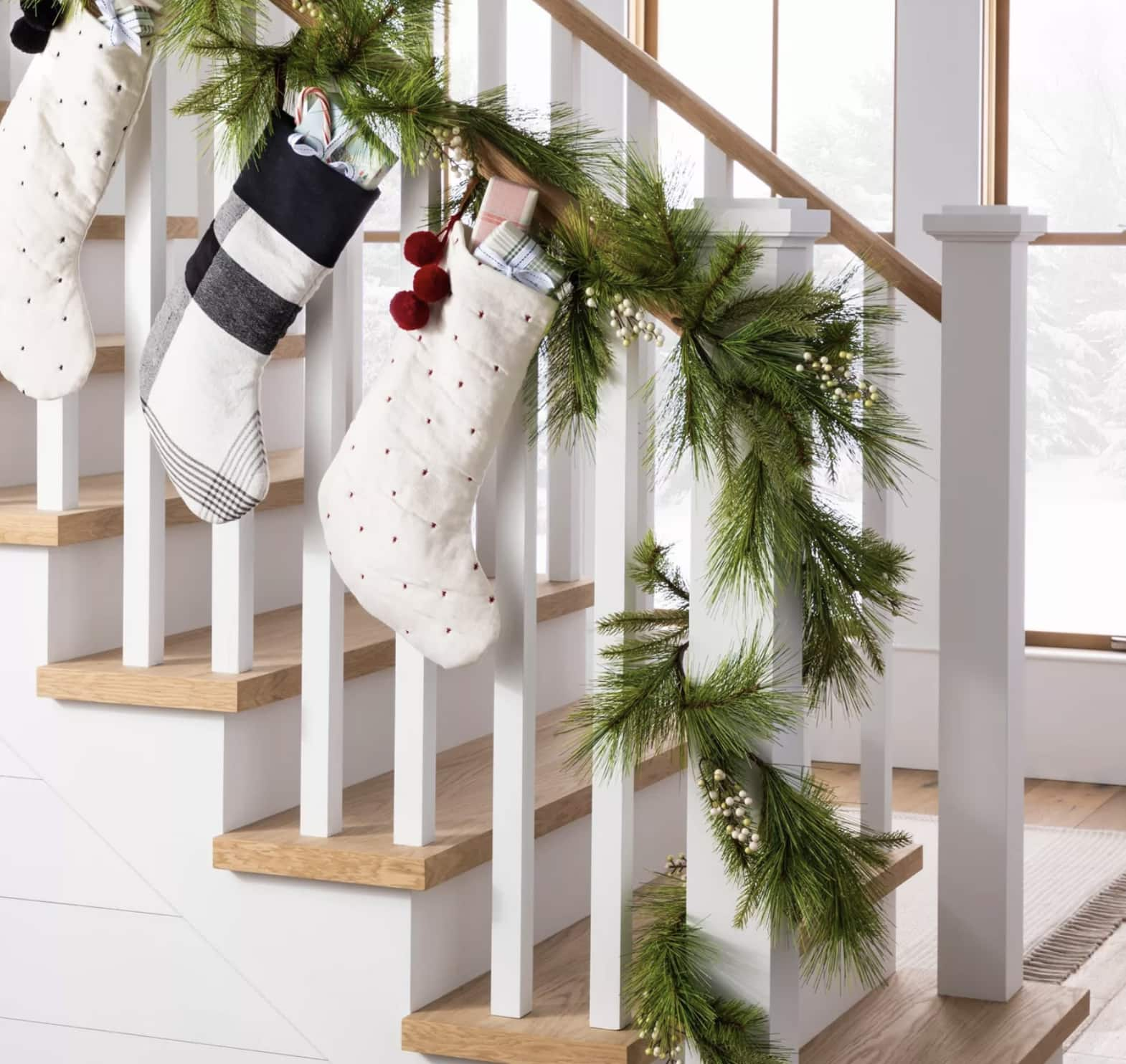 Pine garland wrapped around a staircase with stockings