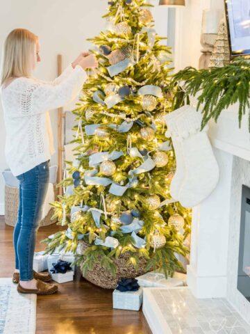 A person adding ribbon to a Christmas tree