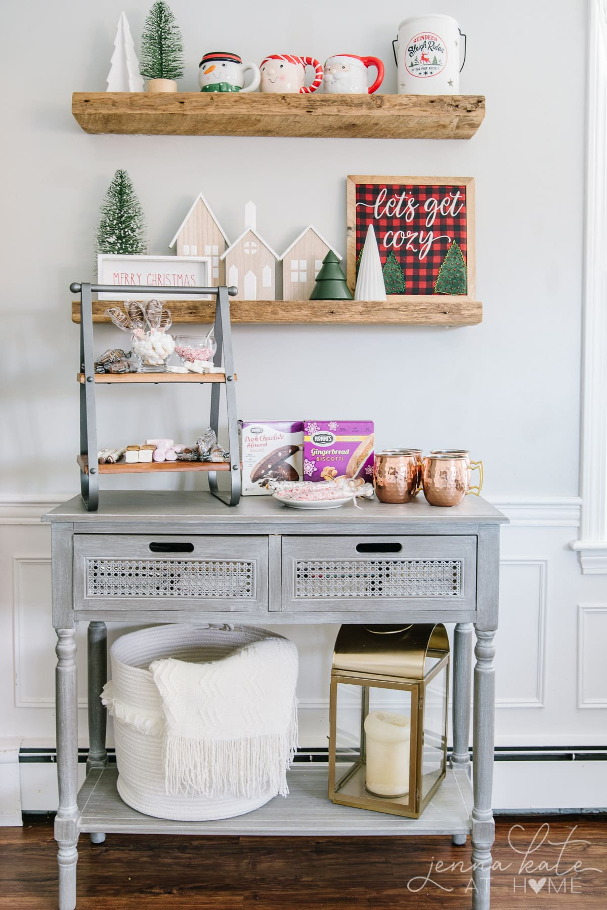 Hot cocoa bar set up for Christmas on a console table with shelves above it
