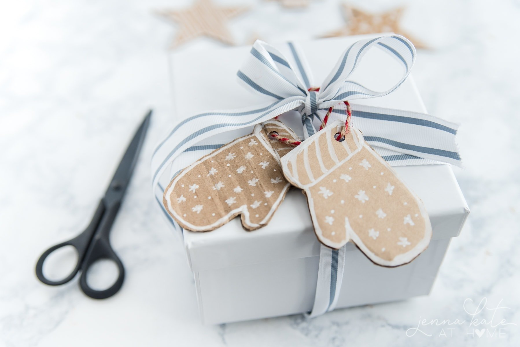 cardboard mitten gift tags hung on a white gift box