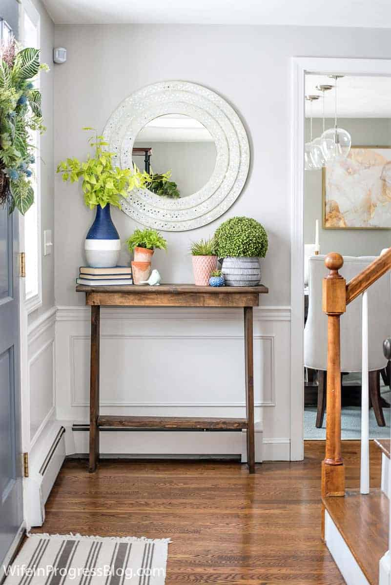 Repose Gray entryway with white wainscoting and wooden console table