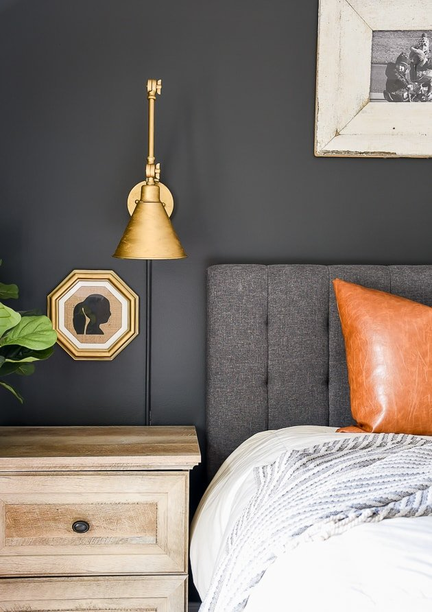 iron ore accent wall with slate  gray headboard and leather pillow on the bed