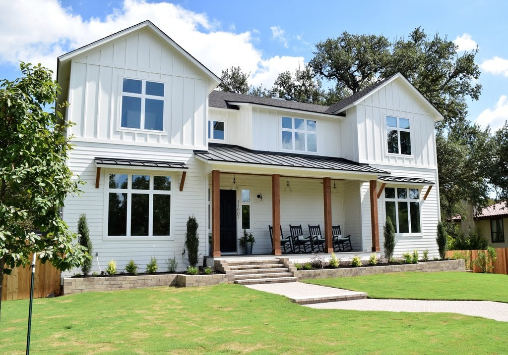 white farmhouse with cedar posts and a green lawn