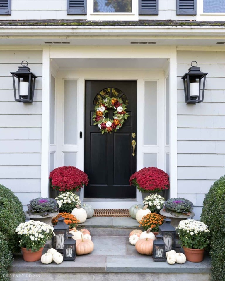 Mums and pumpkins on the front steps of a house