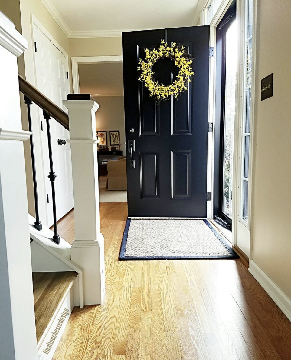 entryway with black front door and walls painted sherwin williams kilim beige