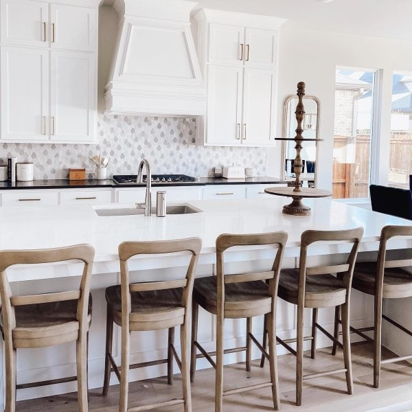 farmhouse style kitchen with wooden counter chairs