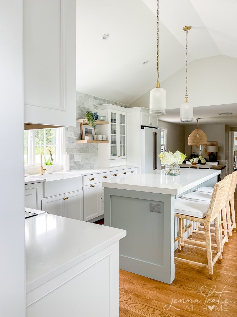 coastal style kitchen with blue island and white cabinets