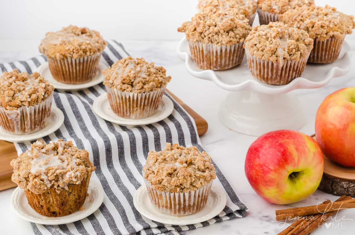 cinnamon apple muffins on a cake stand and cutting board