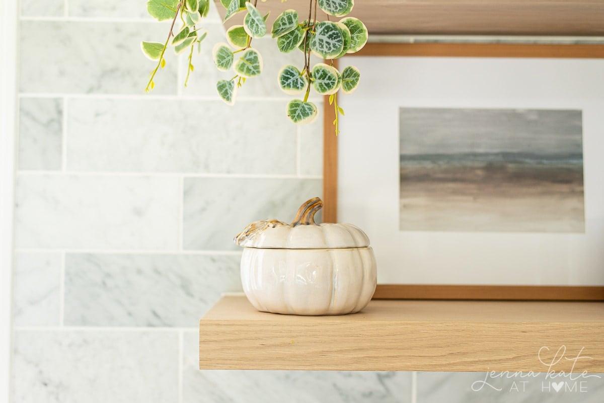 ceramic pumpkin and fall artwork on a floating shelf