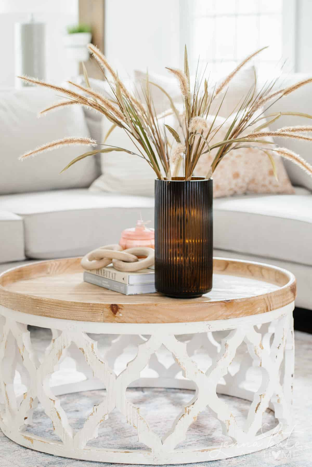 amber vase filled with dry grass on a wooden coffee table