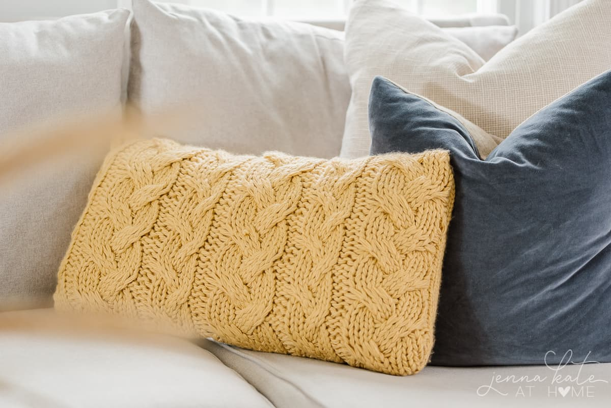 yellow cable knit pillow on a couch